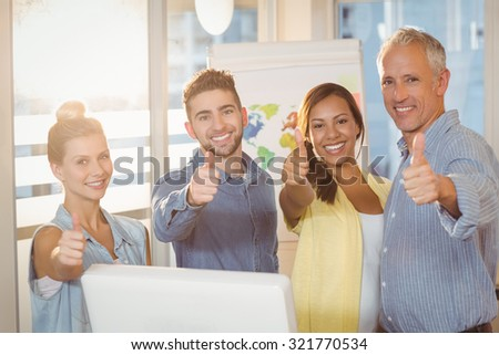 Portrait of smiling business people showing thumbs up in meeting room at creative office - stock photo