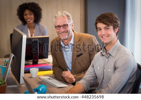 Portrait of smiling business people sitting in office