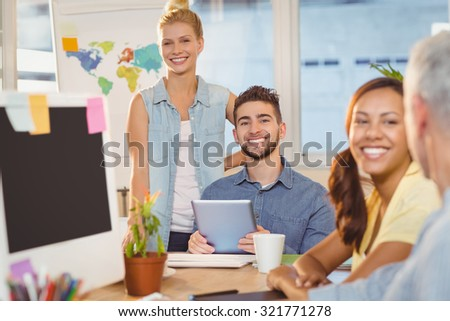 Portrait of smiling business people using digital PC with colleagues working in foreground in creative office - stock photo