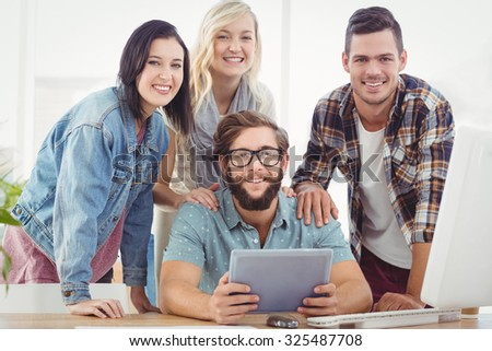 Portrait of smiling business people using digital tablet at desk in office - stock photo