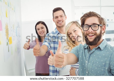 Portrait of smiling business people with thumbs up while standing at creative office - stock photo