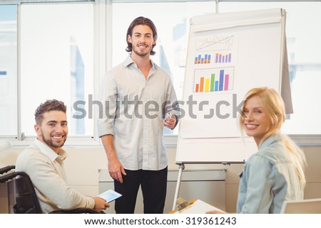 Portrait of smiling business people with whiteboard during meeting in creative office