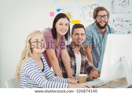 Portrait of smiling business professionals working at computer desk in creative office - stock photo