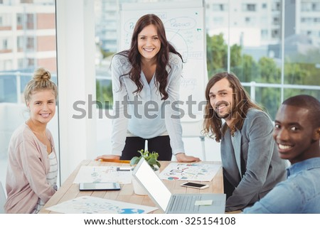 Portrait of smiling business team at desk in office - stock photo