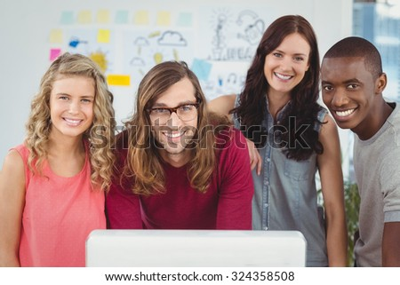 Portrait of smiling business team standing at computer desk in creative office