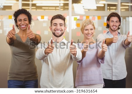 Portrait of smiling business team standing together and gesturing thumbs up in office - stock photo