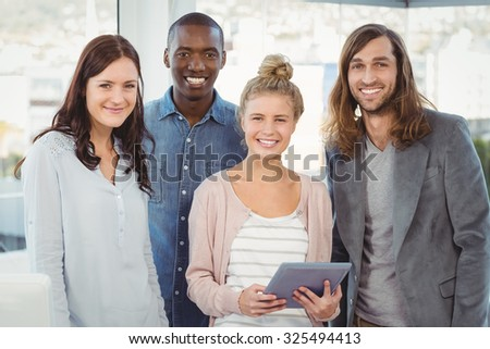 Portrait of smiling business team with woman holding digital tablet at office