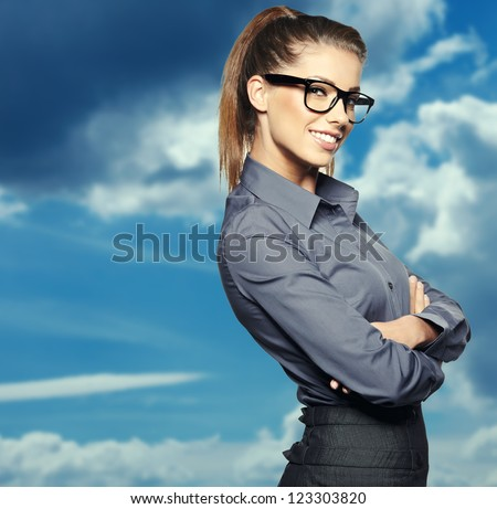 Portrait of smiling business woman, isolated on sky background - stock photo