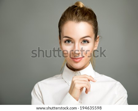 Portrait of Smiling Business Woman Wearing White Shirt against Gray Background - stock photo