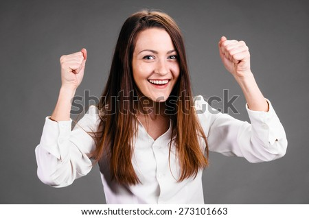 Portrait of smiling business woman with hands up, on gray background