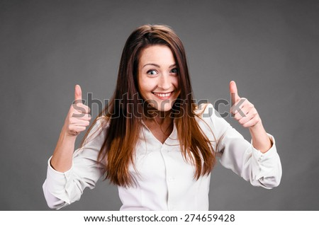 Portrait of smiling business woman with thumbs up, on gray background - stock photo