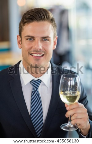 Portrait of smiling businessman holding a beer glass in restaurant