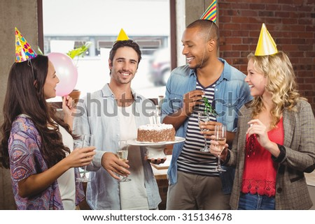 Portrait of smiling businessman holding cake during birthday celebration in office - stock photo