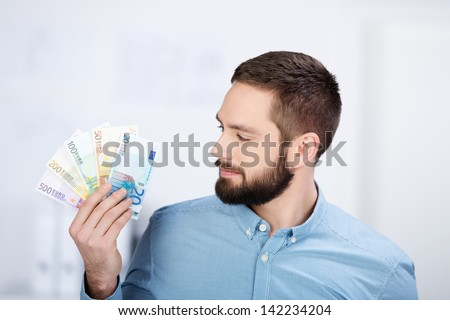 Portrait of smiling businessman holding Euro notes in office - stock photo