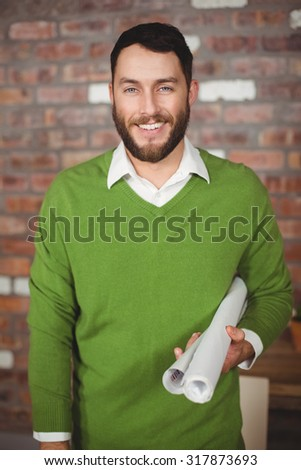 Portrait of smiling businessman holding folded papers in creative office