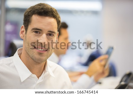 Portrait of smiling businessman in office, looking camera - stock photo