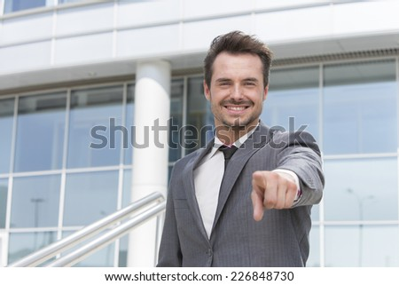 Portrait of smiling businessman pointing at you outside office building - stock photo