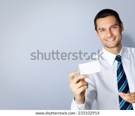 Portrait of smiling businessman showing blank business or plastic credit card, with blank copyspace area for text or slogan, against grey background - stock photo