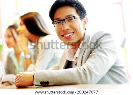 Portrait of smiling businessman sitting in front of colleagues