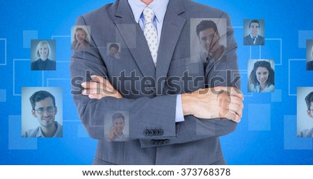 Portrait of smiling businessman standing arms crossed against blue background