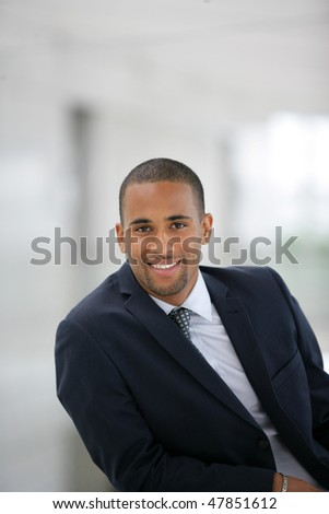 Portrait of smiling businessman standing in hall - stock photo