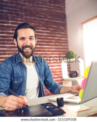 Portrait of smiling businessman using graphic tablet and laptop in creative office - stock photo
