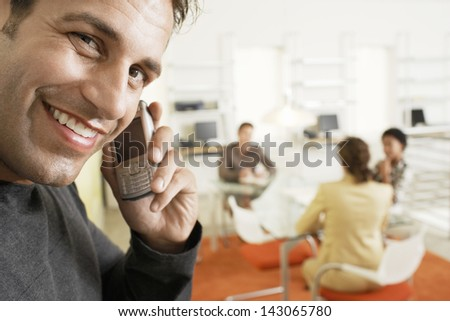 Portrait of smiling businessman using mobile phone with colleagues discussing in background - stock photo