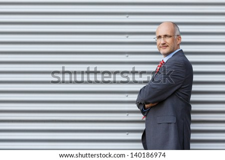 Portrait of smiling businessman with arms crossed - stock photo