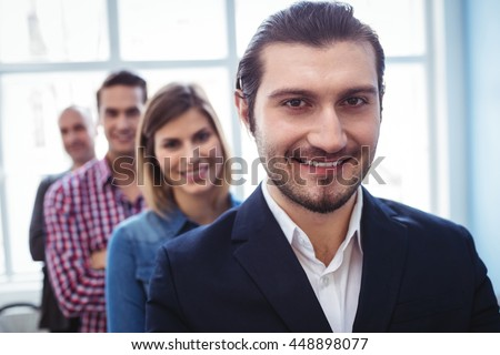 Portrait of smiling businessman with colleagues standing in row at creative office