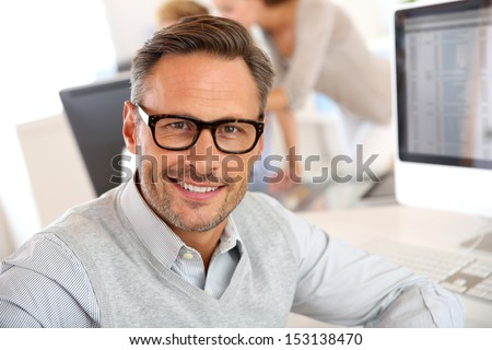 Portrait of smiling businessman with eyeglasses - stock photo