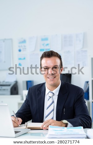 Portrait of smiling businessman working at is table