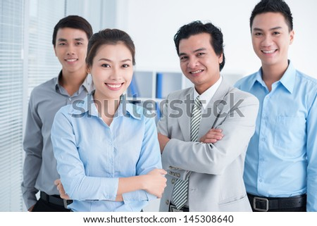 Portrait of smiling businesspeople, standing and posing at camera - stock photo