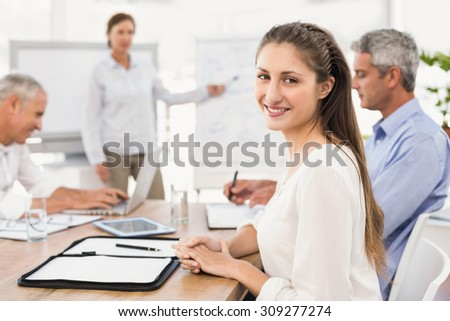 Portrait of smiling businesswoman during a presentation in the office - stock photo