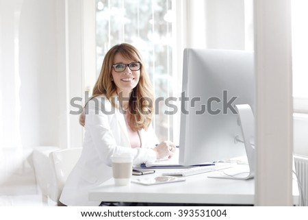 Portrait of smiling businesswoman looking at camera and smiling while working at office in front of computer. - stock photo
