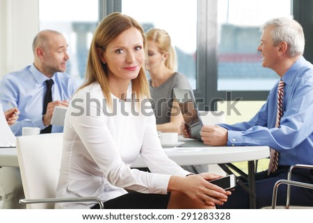 Portrait of smiling businesswoman sitting at meeting and looking at camera while business team working at background.