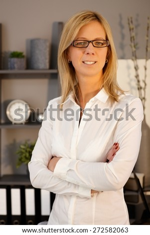Portrait of smiling businesswoman standing arms crossed, looking at camera.