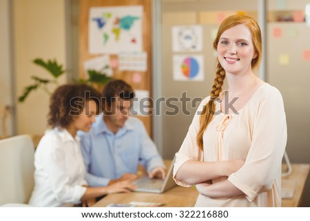 Portrait of smiling businesswoman standing with arms crossed while colleagues working on laptop in background at office