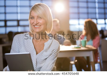 Portrait of smiling businesswoman using digital tablet in creative office - stock photo