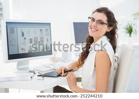 Portrait of smiling businesswoman using digitizer in the office - stock photo