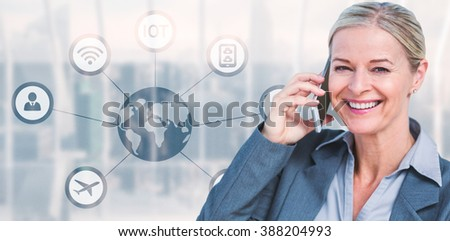 Portrait of smiling businesswoman using mobile phone against room with large window looking on city