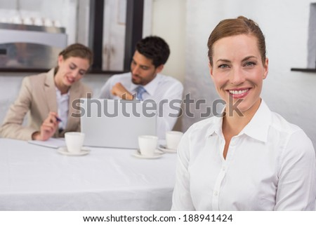 Portrait of smiling businesswoman with colleagues in meeting behind at office desk