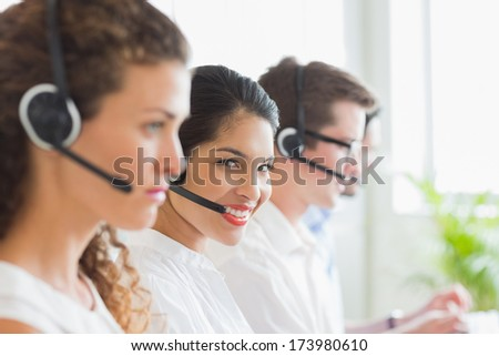 Portrait of smiling businesswoman with colleagues working in call center - stock photo