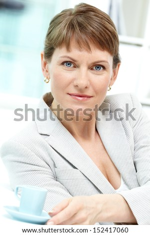Portrait of smiling businesswoman with cup looking at camera - stock photo