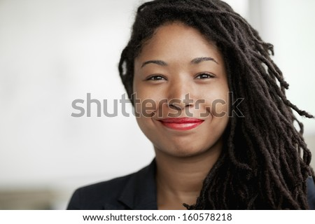 Portrait of smiling businesswoman with dreadlocks - stock photo