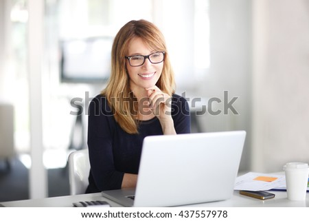 Portrait of smiling businesswoman working on laptop at her workstation. - stock photo