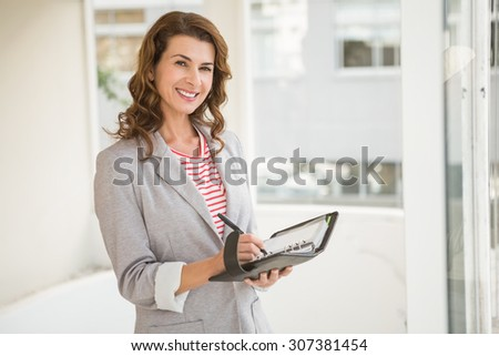 Portrait of smiling businesswoman writing in planner in the office - stock photo