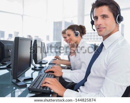 Portrait of smiling call center employee with colleagues behind - stock photo