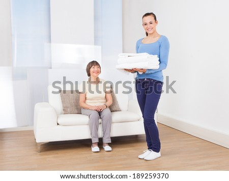 Portrait of smiling caretaker carrying stack of folded towels with senior woman sitting on sofa at nursing home - stock photo