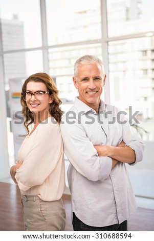 Portrait of smiling casual business colleagues with arms crossed in the office - stock photo