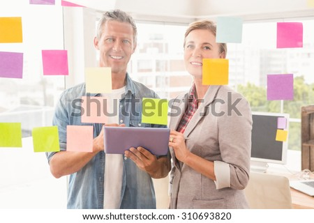 Portrait of smiling casual business colleagues with tablet in the office - stock photo